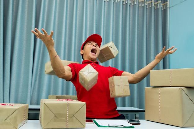 Beschäftigter kurier im büro und viele pakete in der luft. Premium Fotos
