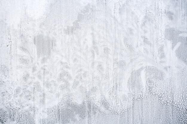 Beschaffenheit des gefrorenen schnees auf fensterglas in form von fantastischen anlagen. Premium Fotos