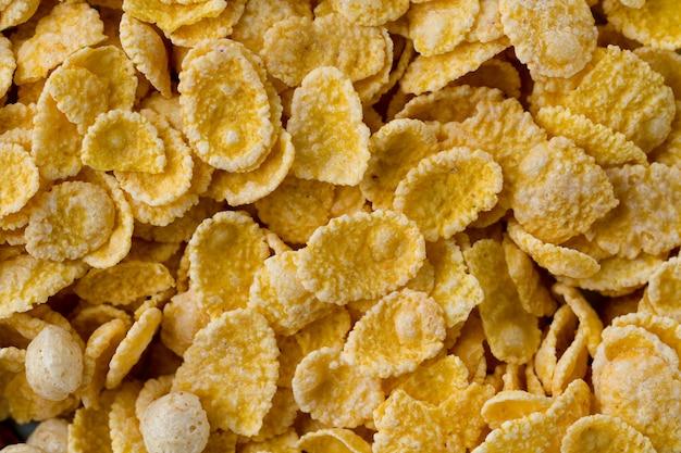 Beschaffenheit von trockenen, bereiften, glasierten gelben corn flakes zum getreidefrühstück. Premium Fotos