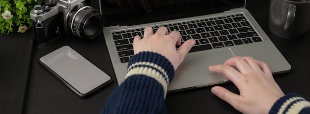 Beschnittener schuss der geschäftsfrau, die mit laptop und smartphone im modernen büroraum arbeitet Premium Fotos