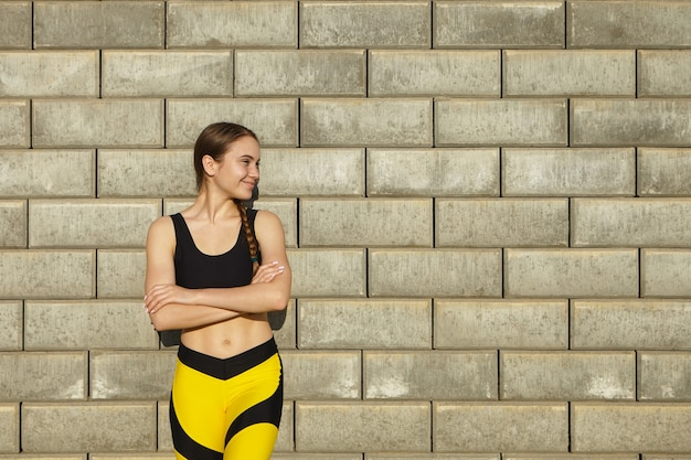 Beschnittener schuss der positiven hinreißenden jungen frau, die trendige schwarze und gelbe sportkleidung trägt, die ruhe im freien hat und gegen leere backsteinmauer mit kopierraum für ihren inhalt aufwirft Kostenlose Fotos