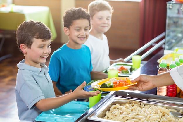 Beschnittenes bild der frau, die essen zu kindern dient Premium Fotos