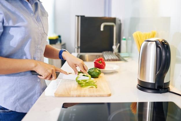 Beschnittenes bild der hausfrau, die am küchentisch steht und paprika für gesunden salat schneidet Premium Fotos