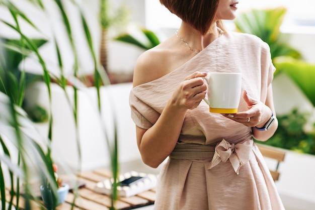 Beschnittenes bild der jungen frau, die mit der großen tasse heißen kaffees oder des tees steht Premium Fotos