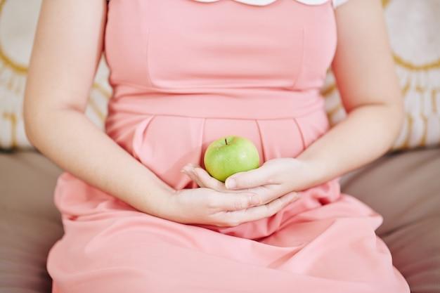 Beschnittenes bild der schwangeren frau, die auf sofa mit grünem apfel in ihren händen sitzt Premium Fotos