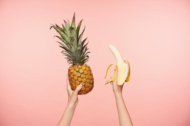 Beschnittenes foto der erhabenen hände der jungen frau mit nackter maniküre, die frische ananas und geschälte banane hält, während über rosa hintergrund lokalisiert wird Kostenlose Fotos