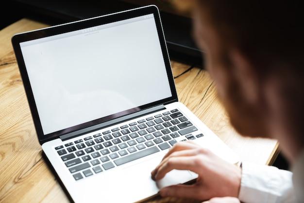 Beschnittenes foto des jungen mannes, der laptop auf holztisch verwendet Kostenlose Fotos