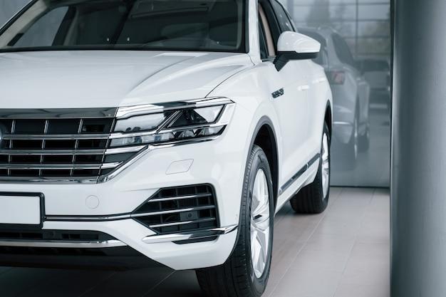 Beschnittenes foto. partikelansicht des modernen weißen luxusautos, das tagsüber drinnen geparkt wird Kostenlose Fotos