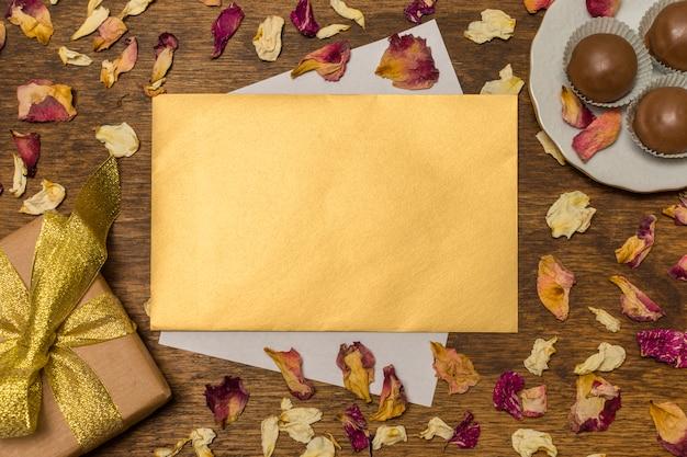 Beschriften sie nahe platte mit süßigkeiten und präsentkarton zwischen trockenen blättern Kostenlose Fotos
