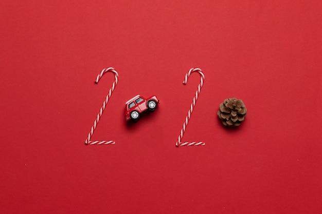 Beschriftung des weihnachts- und neujahrsfeiertags 2020 des roten autospielzeugs der verschiedenen dekoration, tannenzapfen auf einem roten hintergrund Premium Fotos