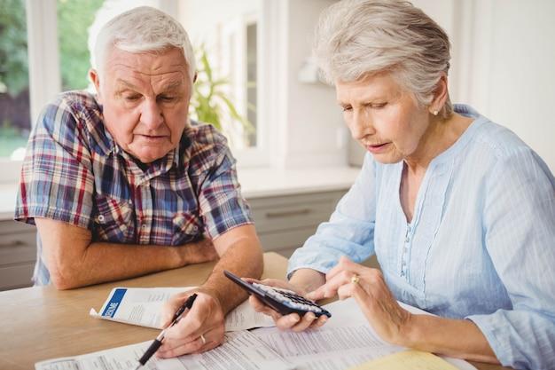 Besorgte ältere paare, die zu hause ihre rechnungen überprüfen Premium Fotos