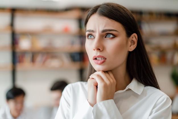 Besorgte geschäftsfrau im büro betroffen über unternehmenszukunft Premium Fotos