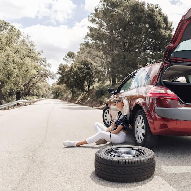 Besorgte junge frau, die nahe dem aufgegliederten auto auf einer leeren straße sitzt Kostenlose Fotos