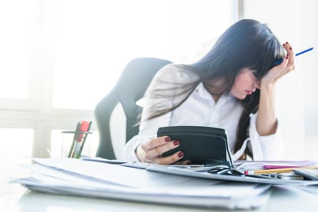 Besorgte junge geschäftsfrau, die taschenrechner über dem arbeitsschreibtisch hält Kostenlose Fotos