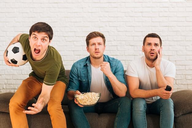 Besorgte männliche freunde, die auf aufpassendem fußballspiel des sofas im fernsehen sitzen Kostenlose Fotos