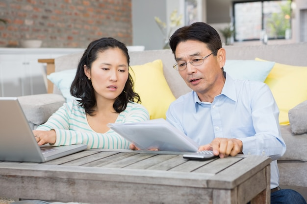 Besorgte paare, die rechnungen im wohnzimmer überprüfen Premium Fotos