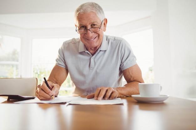 Besorgter älterer mann mit steuerdokumenten zu hause Premium Fotos