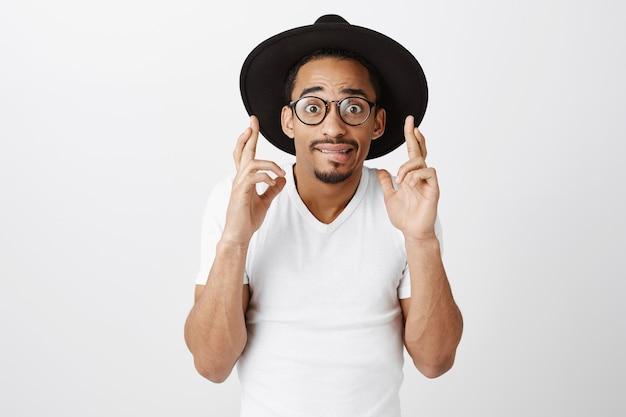 Besorgter afroamerikaner in hipster-hut und lässigem t-shirt kreuzen die finger viel glück und wünschen Kostenlose Fotos