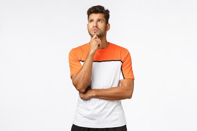 Besorgter, besorgter junger hübscher männlicher athlet in activewear, Premium Fotos