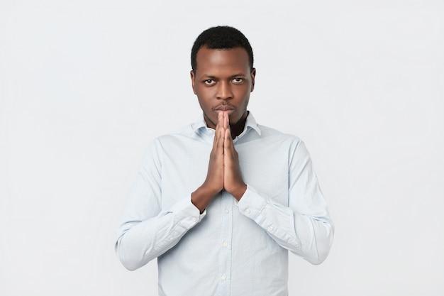 Besorgter junger afroamerikaner legte hände zusammen und bat um hilfe vergebung im gebet Premium Fotos