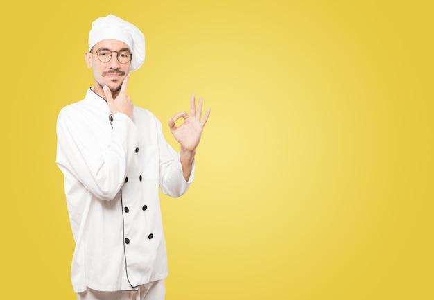 Besorgter junger koch, der zweifelt und eine geste der zustimmung macht Premium Fotos