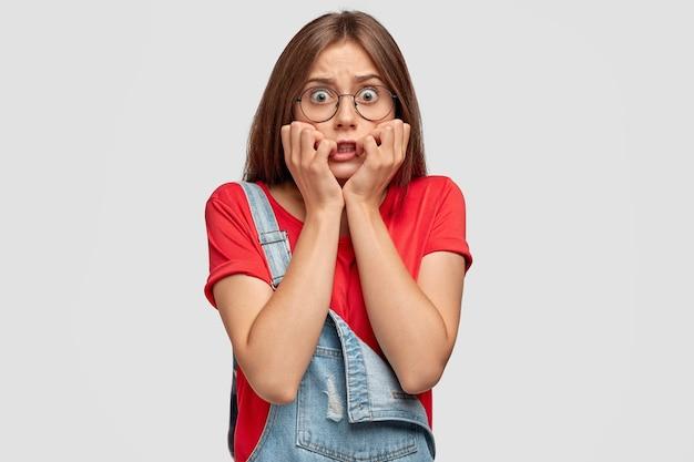 Besorgter teenager mit brille, die gegen die weiße wand aufwirft Kostenlose Fotos