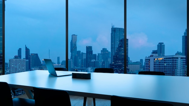 Besprechungsraum und arbeitsplatz mit notebook laptop bequeme arbeitstisch in bürofenstern und bangkok blick auf die stadt. Premium Fotos