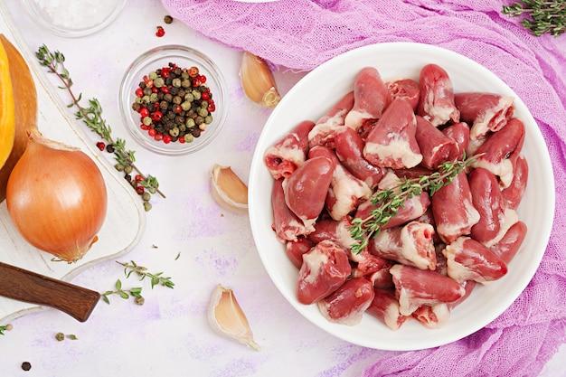 Bestandteile für das kochen von hühnerherzen mit kürbis und tomaten in der tomatensauce. Premium Fotos