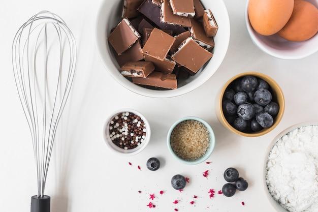 Bestandteile für die herstellung des kuchens wischen auf weißem hintergrund Kostenlose Fotos