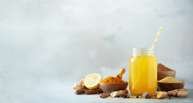 Bestandteile für orange gelbwurzgetränk auf grauem konkretem hintergrund. zitronenwasser mit ingwer, kurkuma, schwarzem pfeffer. Premium Fotos