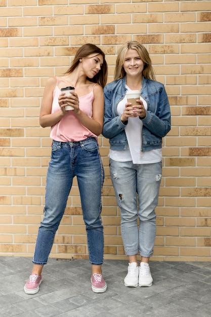 Beste freunde halten ihre tassen kaffee Kostenlose Fotos