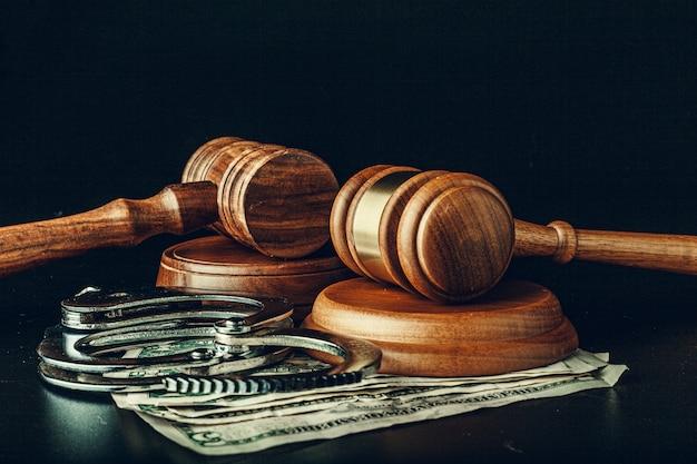 Bestechungsgeld-konzept. dollarbanknoten, -handschellen und -hammer auf tabelle des dunklen schwarzen Premium Fotos