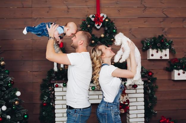 Bestimmtheitsfamilie, die zusammen nahe kamin und geschenken für weihnachten aufwirft Premium Fotos