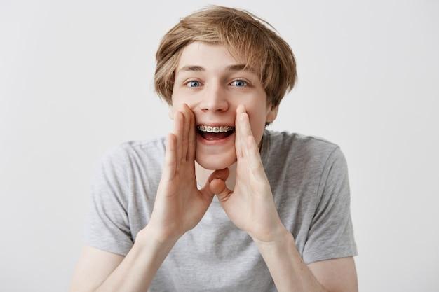 Betäubter überglücklicher kaukasischer männlicher student schreit vor aufregung, hält die hände in der nähe des mundes und freut sich, die universität oder das college zu betreten. emotional glücklich überrascht junger blonder mann schreit wow oder omg Kostenlose Fotos