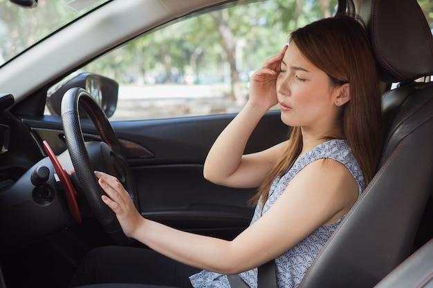 Betont vom asiatischen frauenfahrer, der innerhalb ihres autos sitzt Premium Fotos