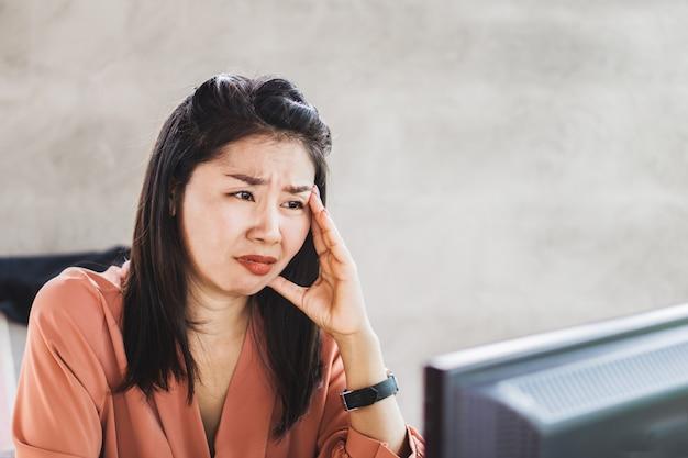 Betonte asiatische arbeitnehmerin, die am schreibtisch schreit Premium Fotos