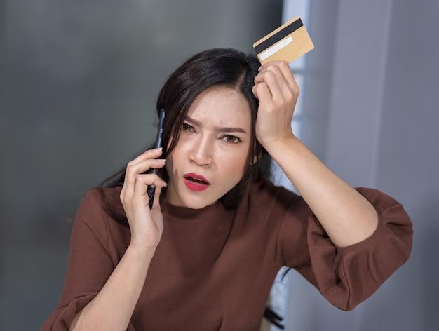 Betonte frau, die telefonisch und holdind kreditkarte zum on-line-einkaufen nennt Premium Fotos