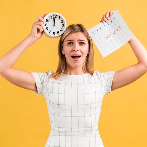 Betonte frau, die uhr und zeitraumkalender hält Kostenlose Fotos
