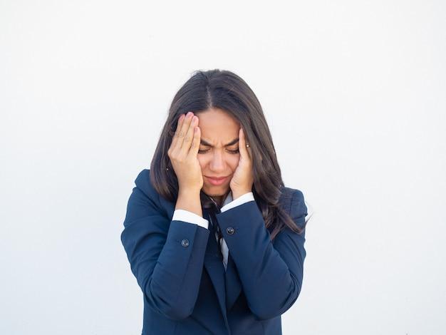 Betonte frustrierte geschäftsfrau, die unter kopfschmerzen leidet Kostenlose Fotos