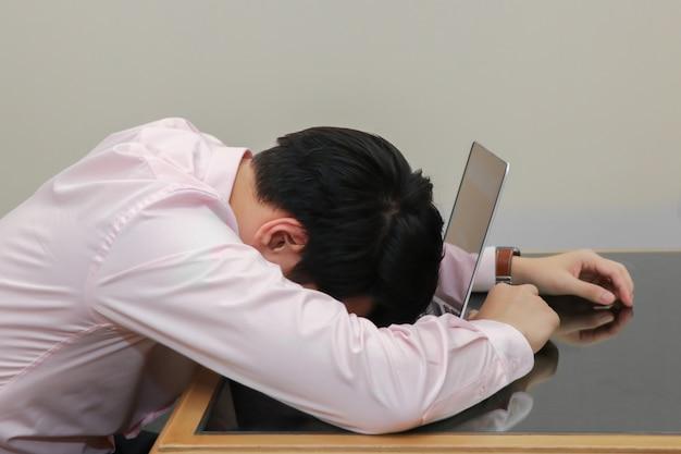 Betonter geschäftsmannschlaf auf seinem laptop mit burnout-syndrom Premium Fotos