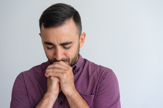 Betonter kerl, der schwierigkeiten sich fühlt und um hilfe betet Kostenlose Fotos