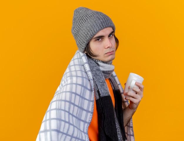 Betrachten des schwachen jungen kranken mannes der kamera, der wintermütze mit schal wickelt, der in plaid eingewickelt tasse tasse tee umwickelt Kostenlose Fotos