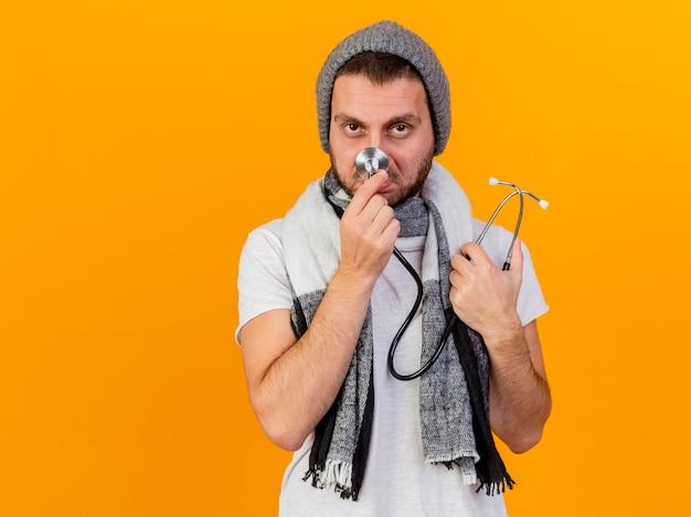 Betrachten des traurigen jungen kranken mannes der kamera, der wintermütze und schal hält und stethoskop auf nase lokalisiert auf gelb hält Kostenlose Fotos