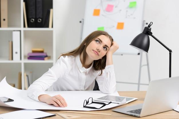 Betrachtete junge geschäftsfrau mit weißbuch; brillen und digitale tablette auf schreibtisch aus holz Kostenlose Fotos