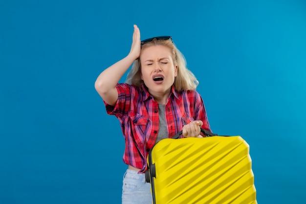 Betroffene junge reisende, die rotes hemd und brille auf kopf hält koffer hält, legte ihre hand auf kopf auf isolierte blaue wand Kostenlose Fotos