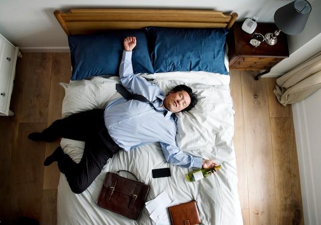 Betrunkener asiatischer geschäftsmann, der einschlafen Premium Fotos