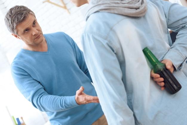 Betrunkener vater bittet verärgert seinen sohn, bier zu geben. Premium Fotos
