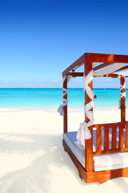 Bett des holzes im karibischen meersand des strandes Premium Fotos