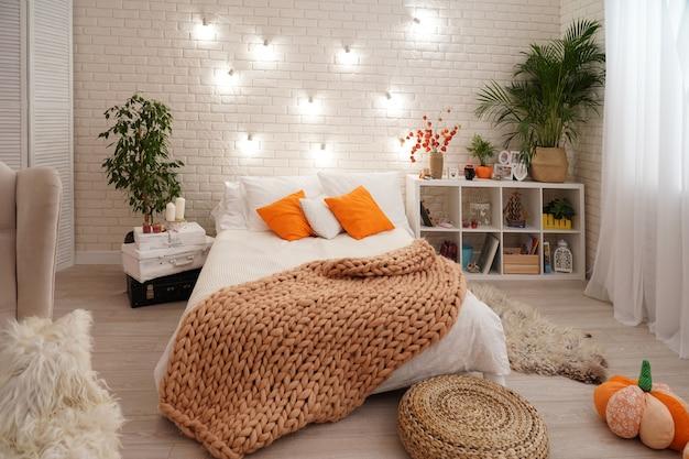 Bett mit heller bettwäsche, bezogen mit einer strickdecke aus grobem garn. Premium Fotos