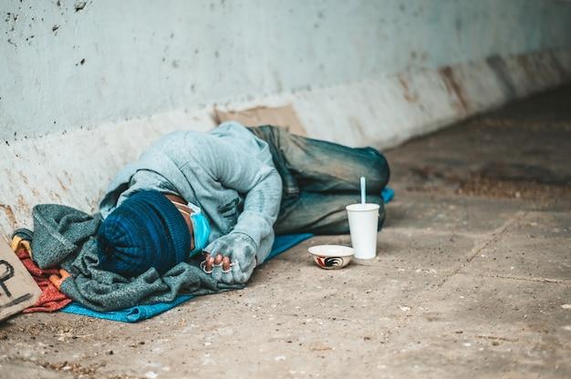 Bettler, die mit schmutziger kleidung am straßenrand liegen. Kostenlose Fotos